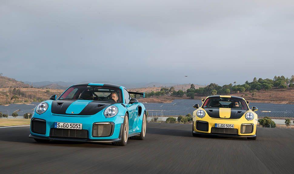 Zwei Porsche 911 GT2 RS fahren versetzt hintereinander auf einer Rennstrecke. Frontale Ansicht