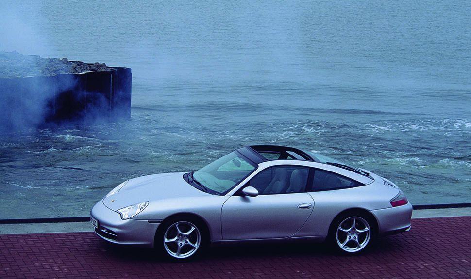 Silberner Porsche 911 996 am Meer von der linken Seite