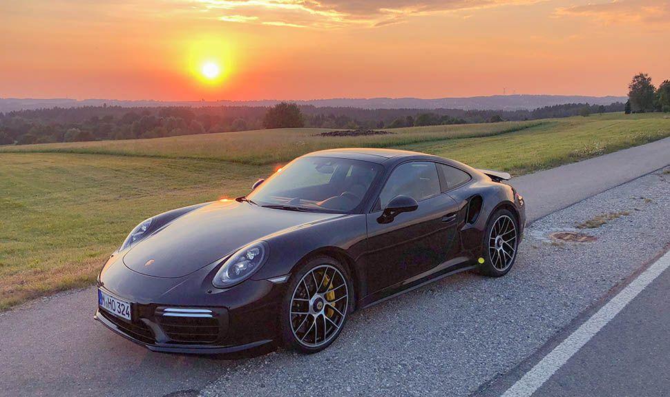Schwarzer Porsche 911 (991) Turbo S steht auf Landstraße im Sonnenuntergang