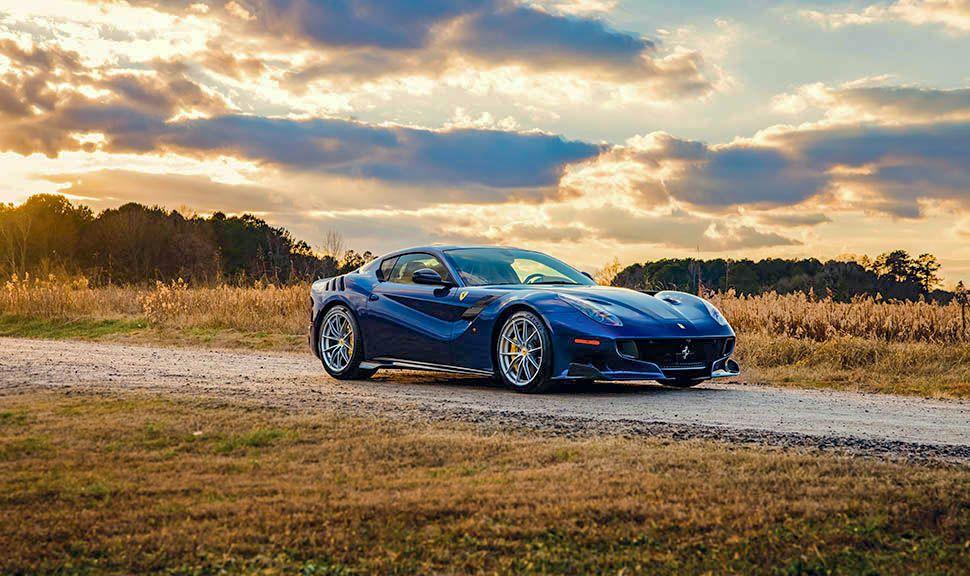 Blauer Ferrari F12 tdf vor spektakulärem Wolkenhimmel