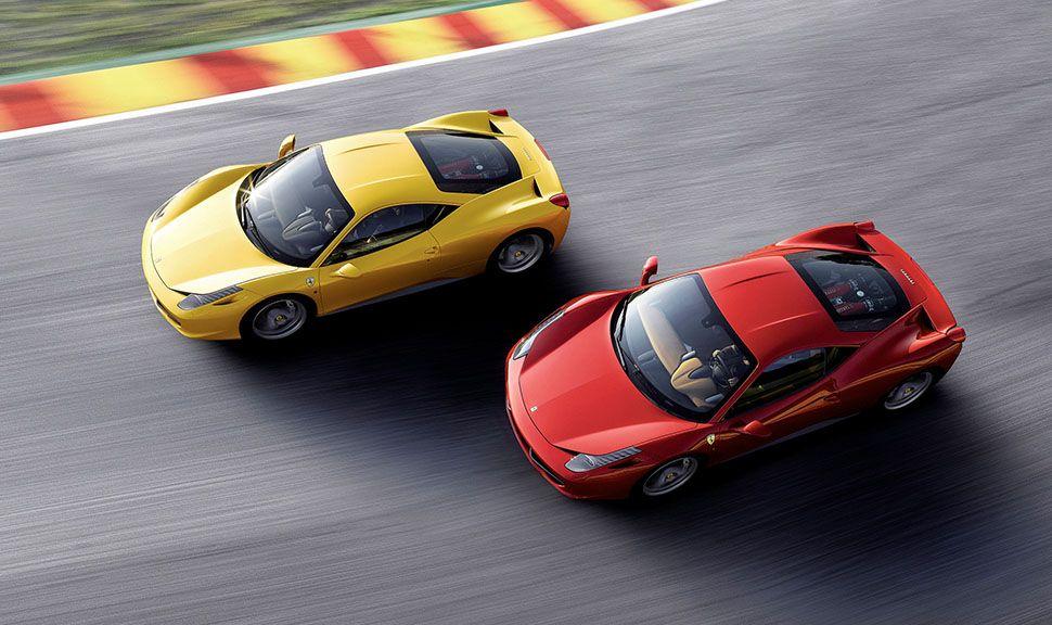 Gelber und roter Ferrari 458 Italia fahren schräg versetzt hintereinander auf der Rennstrecke