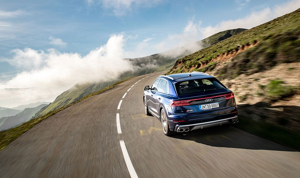 Heckansicht des auf einer Bergstraße fahrenden Audi Q8