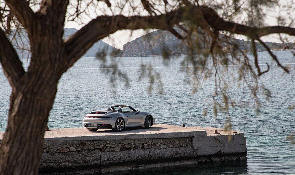 Porsche 911 Carrera S Cabrio in Entfernung am Kai, Baum im Vordergrund