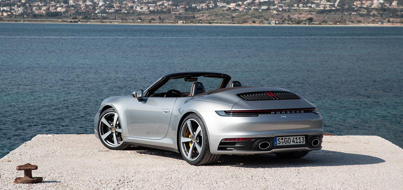 Porsche 911 Carrera S Cabrio in Silber von links hinten am Meer