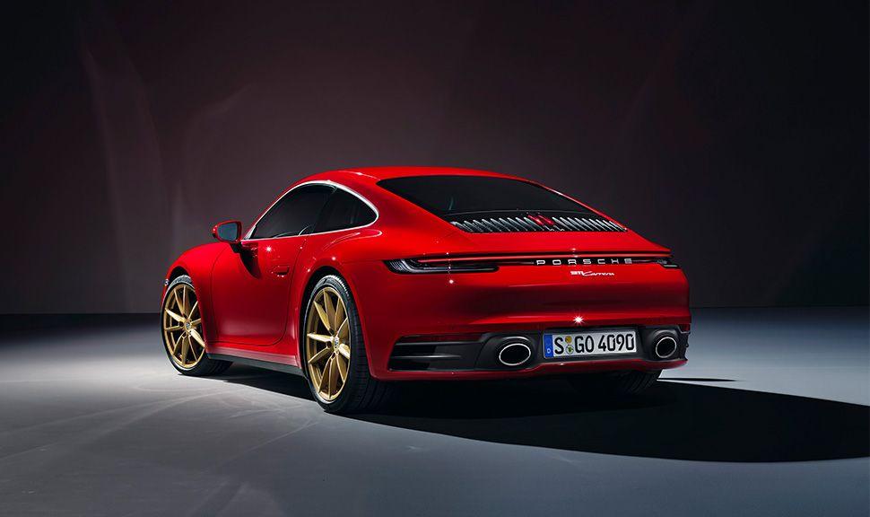 Roter Porsche 911 Carrera 992 mit goldenen Felgen von schräg links hinten