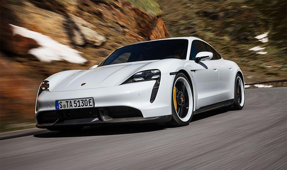 Weißer Porsche Taycan Turbo S fährt auf Bergstraße