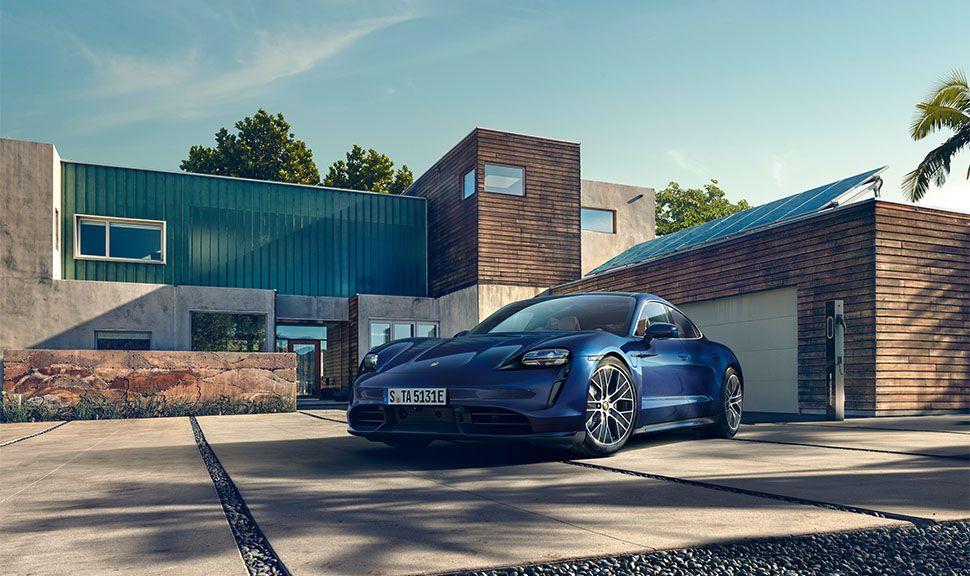 Blauer Porsche Taycan vor Architektur