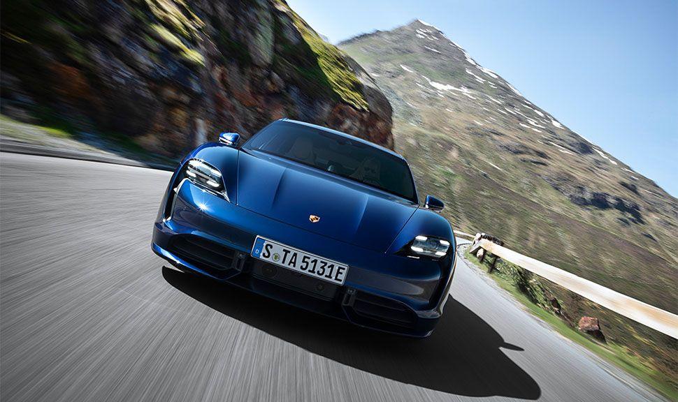 Blauer Porsche Taycan Turbo von vorne auf Bergstraße fahrend