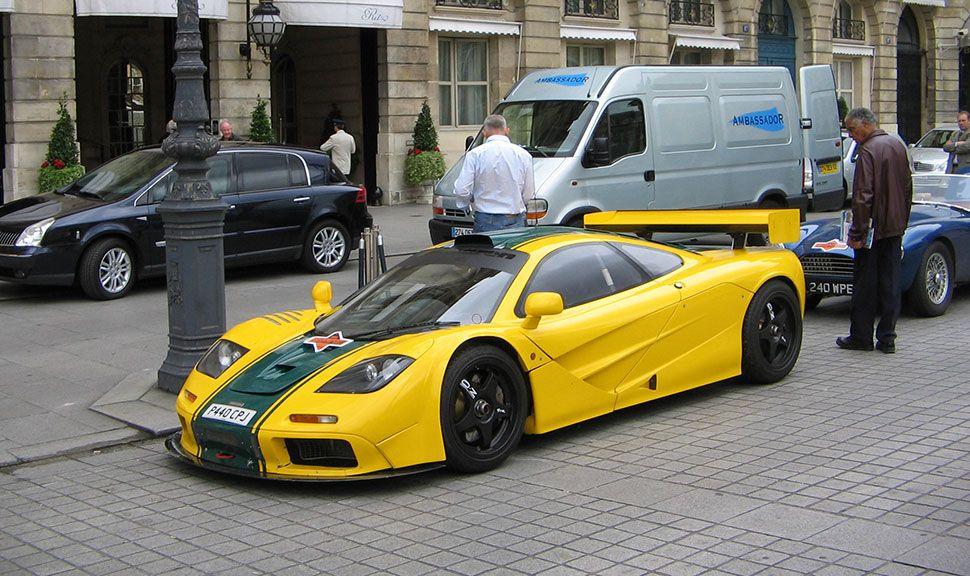 McLaren F1 in Gelb mit dunkelgrünem Racingstreifen auf Straße parkend