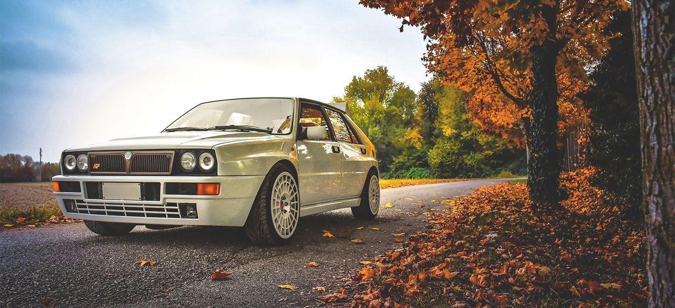 Weißer Lancia Delta HF Integrale von schräg rechts vorne im Herbst