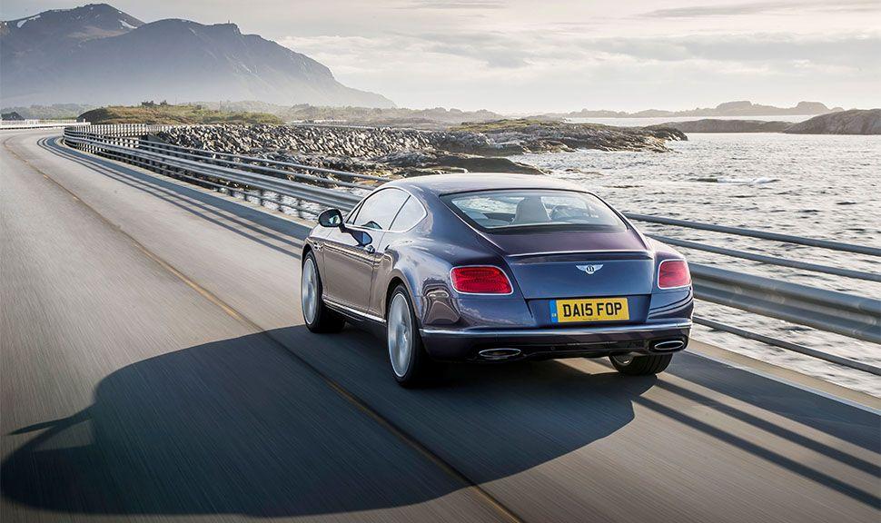 Bentley Continental GT an Küstenstraße fahrend von schräg links hinten