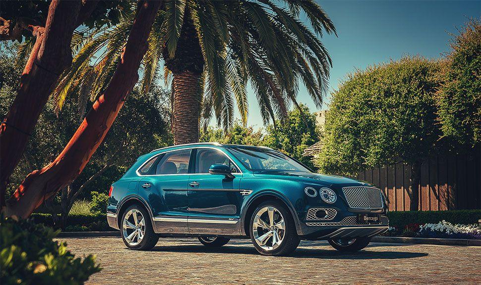 Bentley Bentayga in Türkis unter Palmen