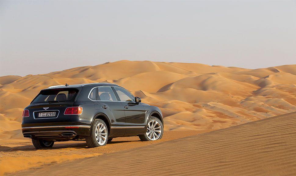 Bentley Bentayga in der Wüste von schräg rechts hinten