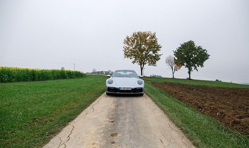 Porsche 911 Carrera in herbstlicher Landschaft von vorne