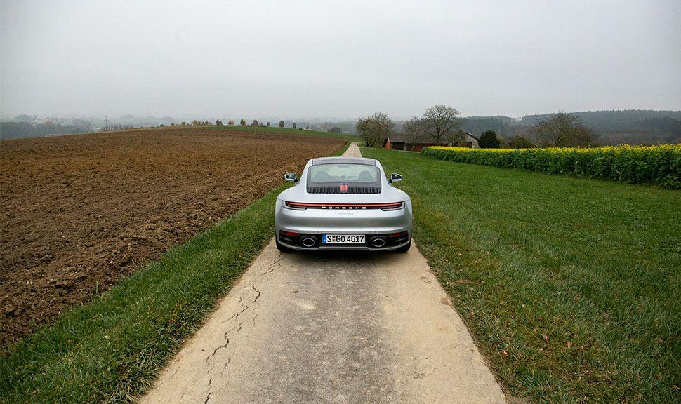 Porsche 911 Carrera in herbstlicher Agrarlandschaft von hinten