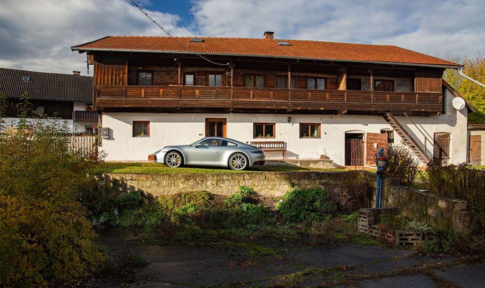 Porsche 911 Carrera vor altem Bauernhaus