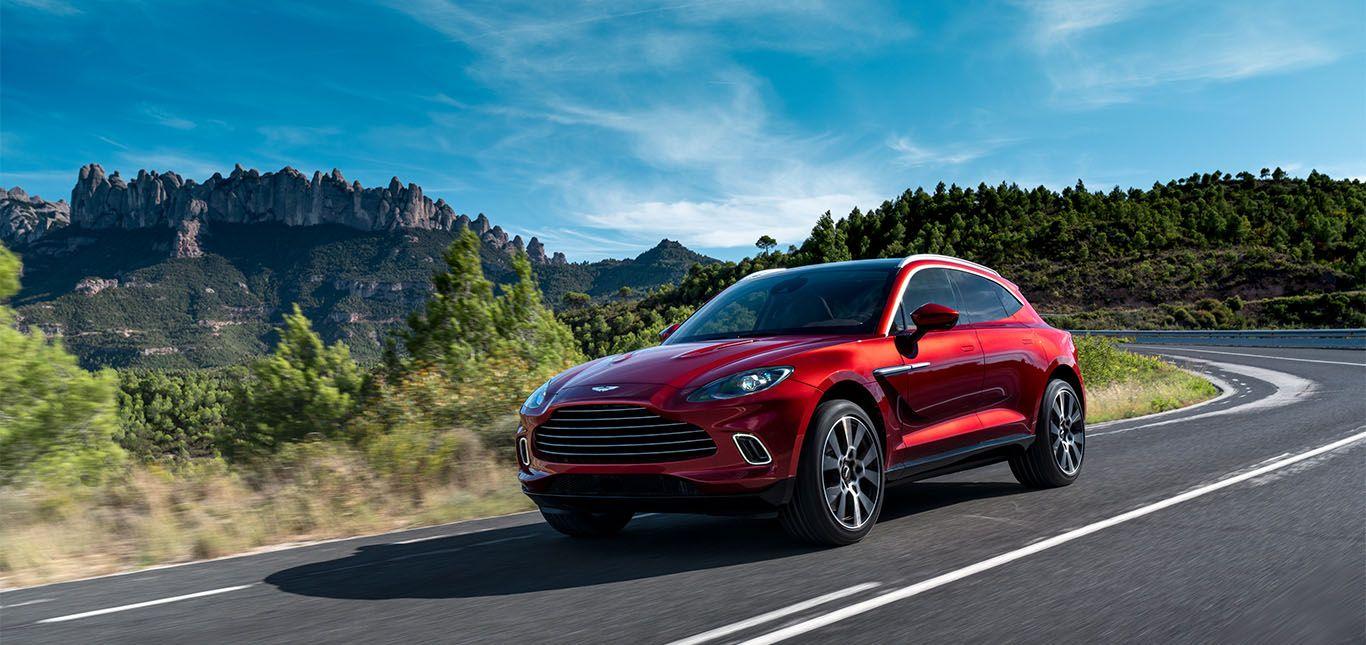 Roter Aston Martin DBX fährt auf Berglandstraße
