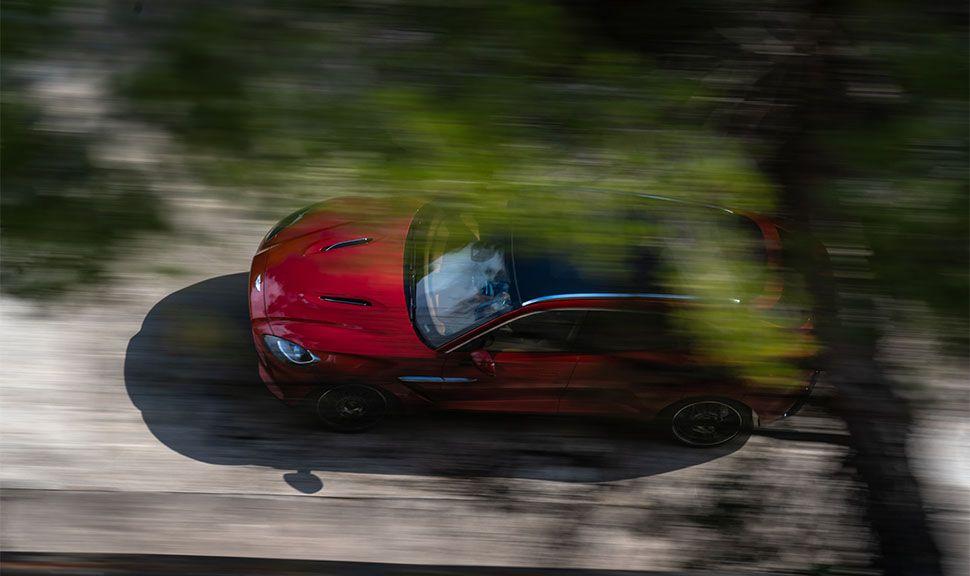 Fahrender Aston Martin DBX von oben durch Baumkrone