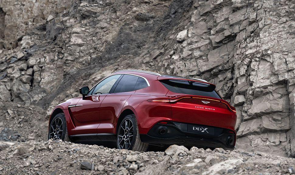 Aston Martin DBX in Steinbruch von schräg links unten hinten