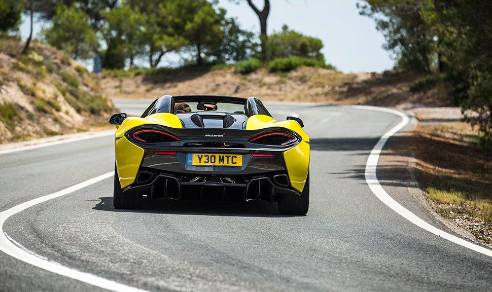 Gelber McLaren 570S von hinten, auf Landstraße fahrend